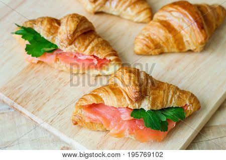 Croissant sandwiches with salmon and green parsley. Croissants with red fish on wooden cutting board. Healthy breakfast. Appetizer. Starter meal