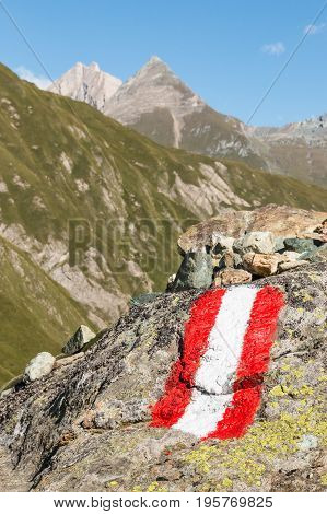 red and white hiking marker on rock in Austrian Alps