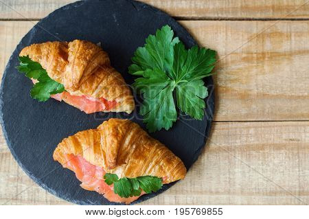 Croissant sandwiches with smoked salmon and parsley on black slate board on wooden table. Sandwiches with red fish and herbs. Breakfast meal
