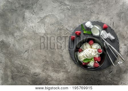 ice cream with raspberries served in black piala with lovely modern scoop, copyspace, topview