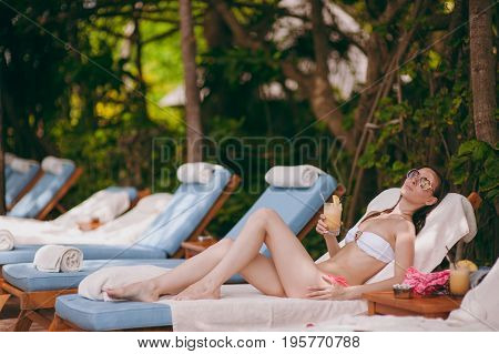 Beautiful Girl Lies On A Deckchair And Drinks A Cocktail