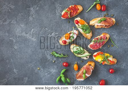 Traditional spanish tapas on black background. Flat lay top view