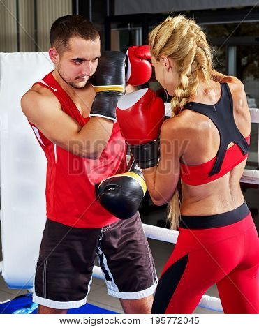 Boxing workout woman in fitness class ring. Sport box exercise two people. Man trainer holding sport mitts in gym. Female box gloves are red backview. Preparation for competitions idea.