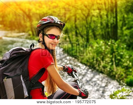 Bikes bicyclist girl rides bicycle into mountains. Woman on your vehicle in mountaineering. Female carries her bike over rocks. Bicyclist looks at his feet. Teenager in a school trip.