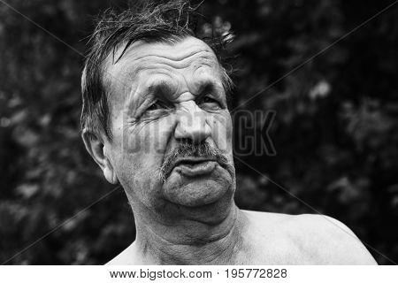Moustached old man close-up portrait in the garden