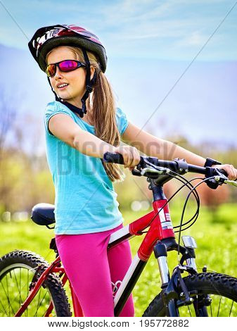 Child traveling bicycle in summer park. Children road bike for running on green grass aganist sky blue. Cycling trip is good for health. Kid travels unaccompanied. Sports program against obesity.