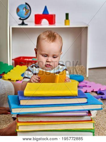 Kid baby boy lying on floor and read book. How to grow genius idea.