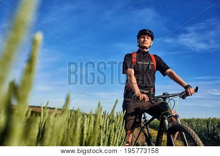 Attractive one cyclist on mountainbike on path near green fields in the countryside in the summer season. Young sportsman dressed in the sportwear, with helmet and red backpack. Beautiful landacpe like a background. Concept of the healthy lifestyle.