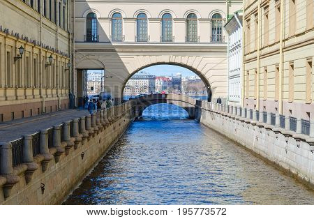 SAINT PETERSBURG RUSSIA - MAY 3 2017: Hermitage Bridge across channel Winter groove St. Petersburg Russia. Unknown people stroll along embankment of canal