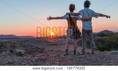 Hugging couple with outstretched arms watching the stunning view of the Namib desert majestic visitor attraction in Namibia Africa. Orange red violet clear sky at the horizon at dusk. Traveling people and adventure.