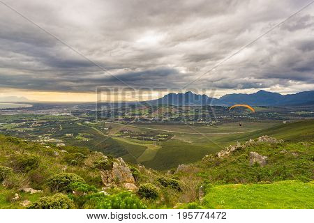 Paraglider Flying Over The Green Mountains Around Cape Town, South Africa. Winter Season, Cloudy And