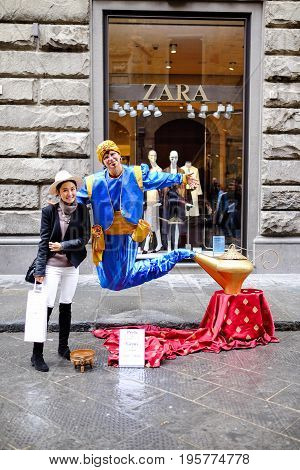 FLORENCE, ITALY - MARCH 27: A Asian tourist taking a photo with Genie and the Magic Lamp street performer in Florence, Italy on March 27, 2015
