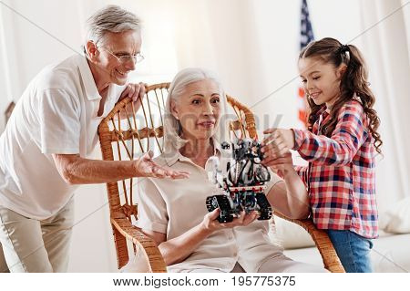 My grandparents. Attractive elderly female keeping eyes wide opened and sitting on chair while examining robot