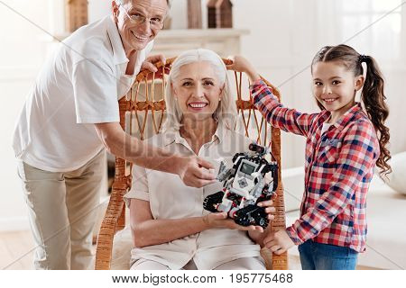 My family. Pretty girl keeping smile on her face and putting hands on the chair while standing near her grandmother
