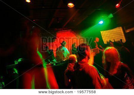 Nightclub dance crowd and DJ in motion