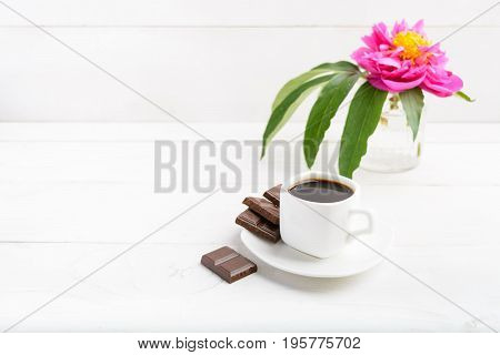 Coffee, Chocolate And Flower In Vase Over White Wooden Table