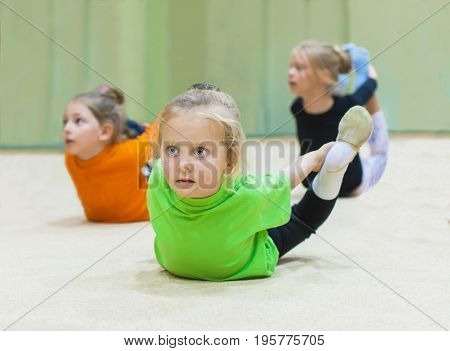 Group of little gymnasts in the gym doing exercises.