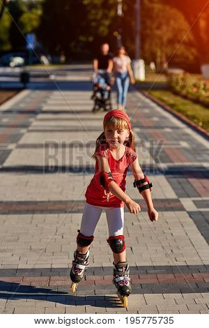 Pretty little girl in red cloth learning to roller skate outdoors on beautiful summer day in city park. Happy childhood concept.