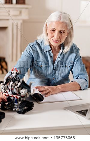 Something interesting. Delighted gray-haired female person keeping smile on her face and putting elbows on the table while looking at robot