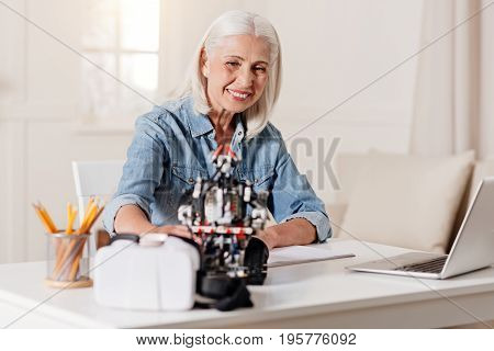 Time for work. Smiling mature woman putting elbows on the table and bowing head while looking at toy