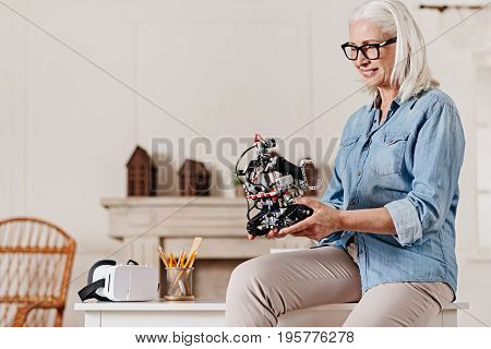 Be always positive. Charming mature woman keeping smile on her face and sitting on the table while looking downwards