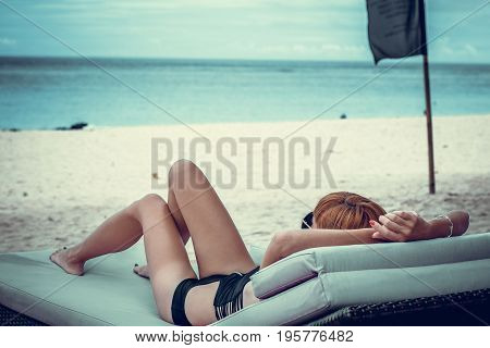 Fashion close up portrait of woman with sunglasses relaxing on deck chair. Sexy summer day spa scene. Tropical Bali island.