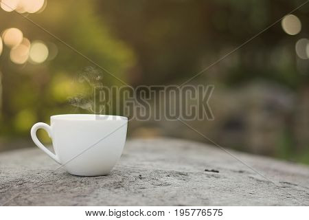 White cup morning coffee in garden and sunrise.