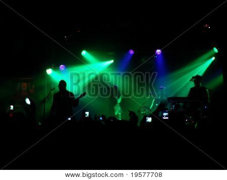 Backlit concert scene with band on stage