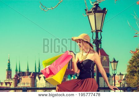 Spending money buying things concept. Fashionable woman resting after big shopping sitting on pole with bags in the old town wearing glamorous outfit and big sun hat