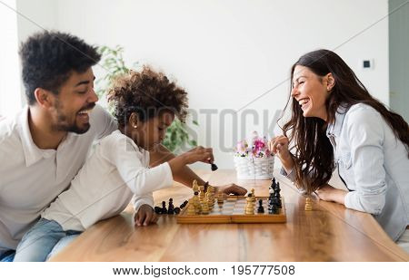 Happy family playing chess together at their home