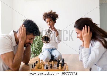 Mother and father trying to play game of chess while their child plays trumpet