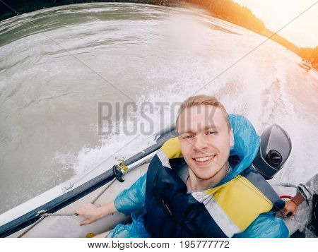 tourist man sitting in a boat and happy, a boat with a motor rides at high speed along the river. Concept rafting