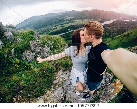 Guy and girl tourists are happy, hug and do selfie on action camera on background of mountains, forests. Concept kiss and travel. Russia, Altai Mountains.