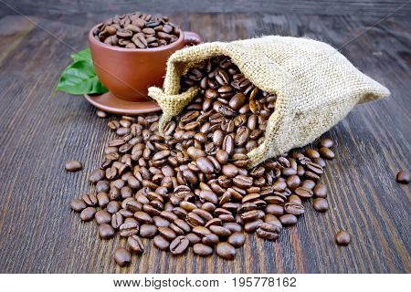 Bag of black coffee beans, brown cup on the background of a dark wooden board