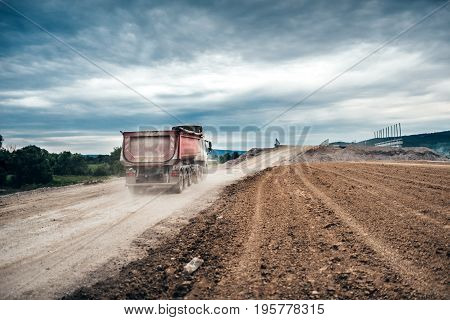 Industrial Dumper Trucks Working On Highway Construction Site, Loading And Unloading Gravel And Eart