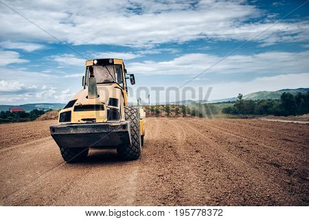 Vibratory Soil Compactor During Highway Building. Industrial Roadworks With Heavy-duty Machinery