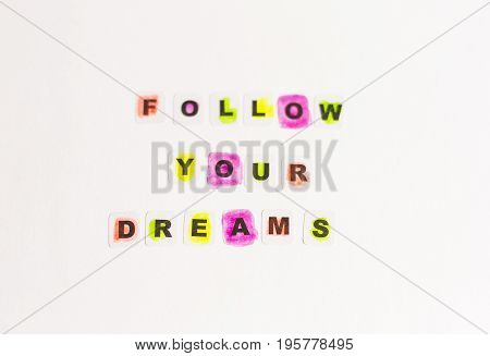 Follow your dreams message written in black letters on neutral background