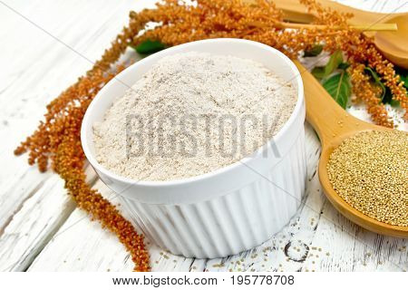Amaranth flour in white bowl, spoons with grain, brown flower with leaves on the background of wooden boards