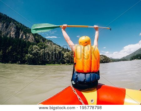 man sits on the edge of a rafting boat in rescued jelly and a protective helmet, rejoices, raises his hands upwards with the lend, a rear view. Concept of active summer.