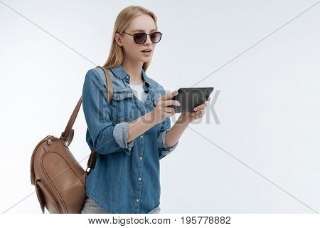 Close your mouth. Attentive woman standing in semi position over white background and keeping tablet in both hands while looking downwards
