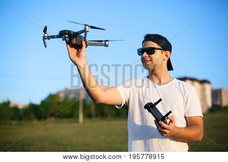 Happy smiling man holds small compact drone and remote controller in his hands. Pilot launches quadcopter from his palm. Drone ready to go on gps