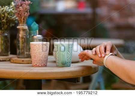 Someone is getting late. Woman checking time on his watch while waiting for him having a cup of coffee
