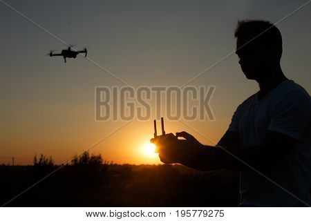 Silhouette of a man piloting drone in the air with a remote controller in his hands on sunset. Pilot takes aerial photos and videos with quadcopter from above. Copter on background