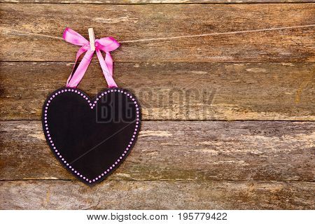 Blackboard Heart With Pink Border And Ribbon On Clothespin Against Rustic Old Wooden Background