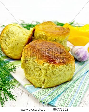 Pumpkin Scones with garlic and dill on a green towel, slices of pumpkin on the background light wooden boards