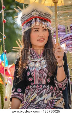 CHIANGMAI THAILAND - JANUARY 25 2015: Hill tribe girl holding white paper umbrella in parade of 22nd Traditional Skirt Fabric and The Indigenous Product and Culture Festival in Mae Chaem Chiangmai Thailand