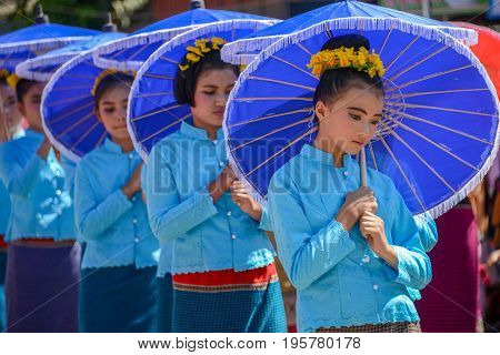 CHIANGMAI THAILAND - JANUARY 25 2015: Indigenous little girls with traditional costume holding umbrella and dancing in traditional style in parade of 22nd Traditional Skirt Fabric and The Indigenous Product and Culture Festival in Mae Chaem Chiangmai Thai