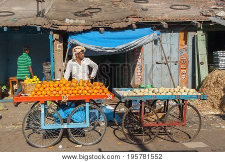 MYSORE, INDIA - FEB 18, 2017: Oranges and other fruits on marketplace of a trader on city street market on February 18, 2017. Mysore of Karnataka has a population of 900000