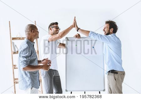 Businessman Giving High Five To Colleague During Strategy Discussion In Office
