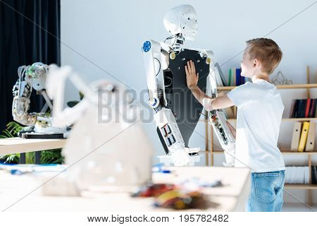Good job. Fair-haired pre-teen boy standing near a human robot and examining its front part while a white warrior robot toy standing in the foreground, being not in the focus